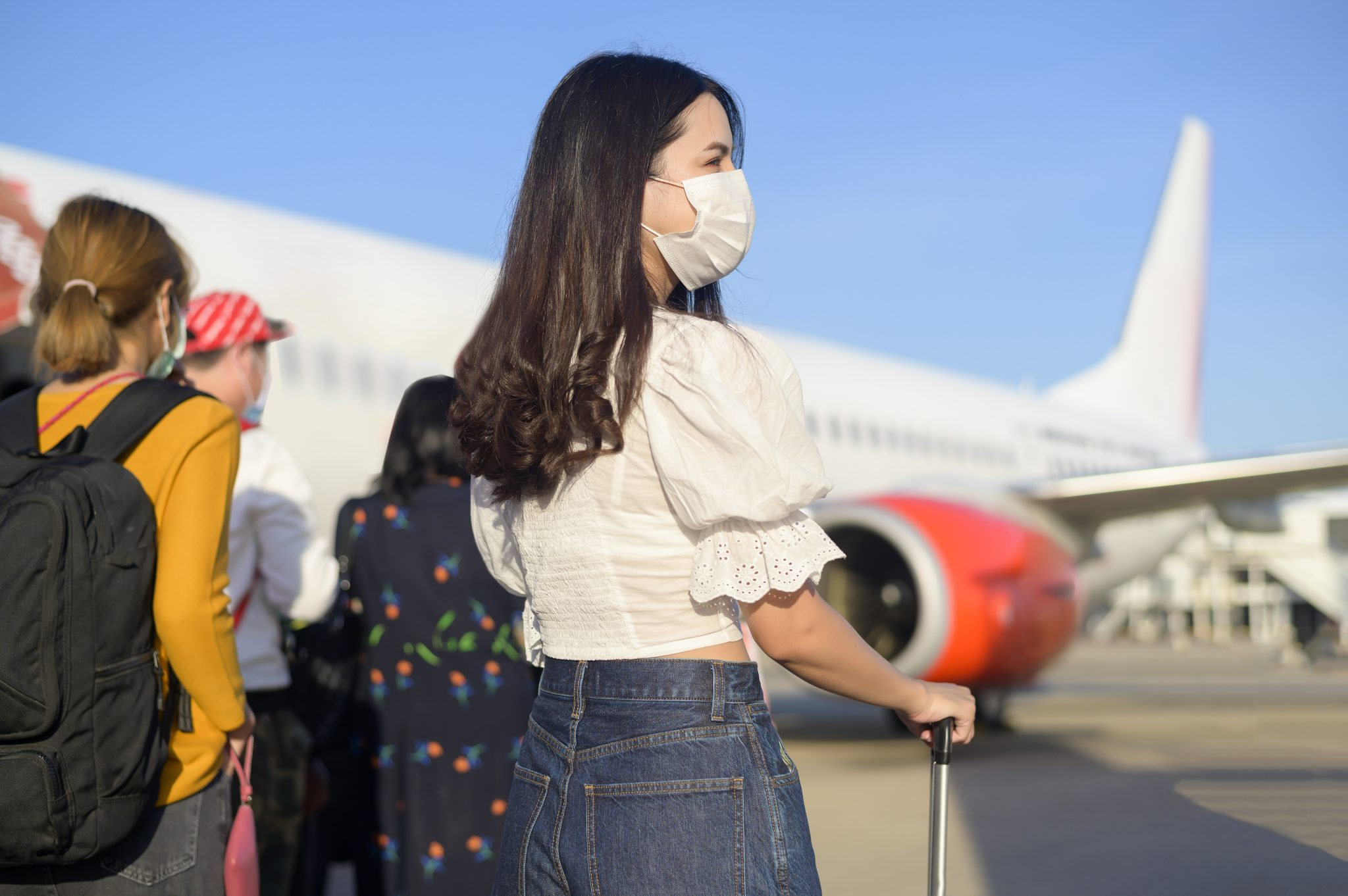 A young woman traveler wearing protective mask getting in airplane and ready to take off, travel under Covid-19 pandemic, safety travels, social distancing protocol, New normal travel concept